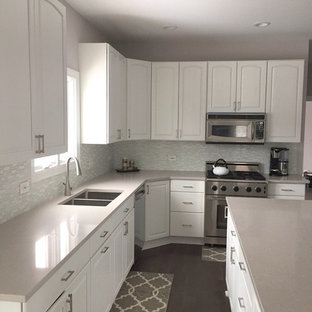 Large kitchen pictures - Inspiration for a large l-shaped dark wood floor kitchen remodel in Chicago with a double-bowl sink, white cabinets, quartz countertops, white backsplash and an island