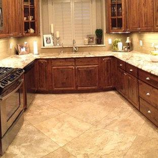 ニューオリンズの中サイズのトラディショナルスタイルのおしゃれなキッチン (アンダーカウンターシンク、レイズドパネル扉のキャビネット、中間色木目調キャビネット、御影石カウンター、ベージュキッチンパネル、ガラスタイルのキッチンパネル、シルバーの調理設備の、セラミックタイルの床、アイランドなし、ベージュの床、ベージュのキッチンカウンター) の写真
