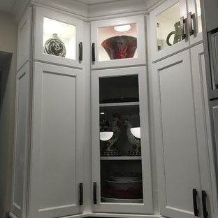 他の地域の大きいモダンスタイルのおしゃれなキッチン (アンダーカウンターシンク、落し込みパネル扉のキャビネット、白いキャビネット、御影石カウンター、マルチカラーのキッチンパネル、トラバーチンの床、シルバーの調理設備の、淡色無垢フローリング、ベージュの床) の写真