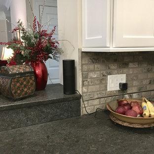 他の地域の広いモダンスタイルのおしゃれなキッチン (アンダーカウンターシンク、落し込みパネル扉のキャビネット、白いキャビネット、御影石カウンター、マルチカラーのキッチンパネル、トラバーチンのキッチンパネル、シルバーの調理設備、淡色無垢フローリング、ベージュの床) の写真