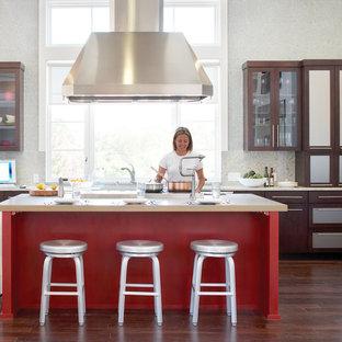 Idee per una cucina chic con ante di vetro, ante in legno bruno, top in granito, paraspruzzi in lastra di pietra, elettrodomestici in acciaio inossidabile, parquet scuro e isola