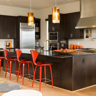 Inspiration for a midcentury l-shaped kitchen in Seattle with dark wood cabinets, granite benchtops, stainless steel appliances, light hardwood floors, with island, flat-panel cabinets, beige splashback and stone slab splashback.