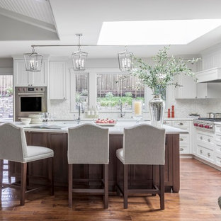 This is an example of a large traditional l-shaped open plan kitchen in San Francisco with a farmhouse sink, shaker cabinets, white cabinets, quartz benchtops, white splashback, mosaic tile splashback, panelled appliances, medium hardwood floors, with island and brown floor.
