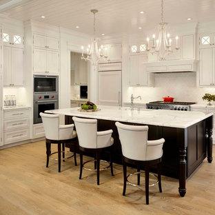 Diseño de cocina en L, tradicional, grande, abierta, con puertas de armario blancas, encimera de mármol, salpicadero blanco, suelo de madera clara, una isla, armarios estilo shaker, electrodomésticos con paneles, fregadero sobremueble y salpicadero de azulejos de cerámica