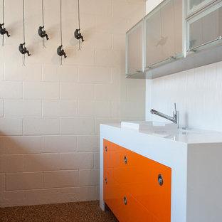Zweizeilige Moderne Wohnküche mit flächenbündigen Schrankfronten, orangefarbenen Schränken, Mineralwerkstoff-Arbeitsplatte, Küchenrückwand in Weiß, Rückwand aus Porzellanfliesen und Küchengeräten aus Edelstahl in San Francisco