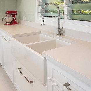 シドニーの中くらいのインダストリアルスタイルのおしゃれなキッチン (エプロンフロントシンク、シェーカースタイル扉のキャビネット、白いキャビネット、クオーツストーンカウンター、緑のキッチンパネル、ガラス板のキッチンパネル、シルバーの調理設備、淡色無垢フローリング) の写真