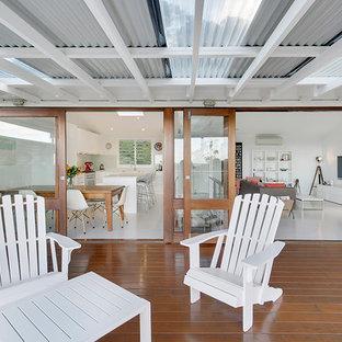 シドニーの中サイズのインダストリアルスタイルのおしゃれなキッチン (エプロンフロントシンク、シェーカースタイル扉のキャビネット、白いキャビネット、クオーツストーンカウンター、緑のキッチンパネル、ガラス板のキッチンパネル、シルバーの調理設備の、淡色無垢フローリング) の写真