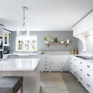 This is an example of a medium sized farmhouse u-shaped open plan kitchen in Other with a belfast sink, beaded cabinets, composite countertops, black appliances, limestone flooring, a breakfast bar, beige floors, white worktops and white cabinets.