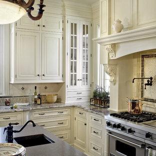 Imagen de cocina tradicional con encimera de granito, electrodomésticos de acero inoxidable, fregadero bajoencimera, armarios con paneles con relieve, puertas de armario beige, salpicadero multicolor y salpicadero de piedra caliza