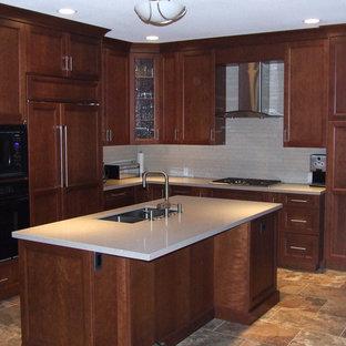 バンクーバーの中サイズの地中海スタイルのおしゃれなキッチン (ダブルシンク、落し込みパネル扉のキャビネット、濃色木目調キャビネット、クオーツストーンカウンター、ベージュキッチンパネル、ボーダータイルのキッチンパネル、黒い調理設備、トラバーチンの床、マルチカラーの床) の写真