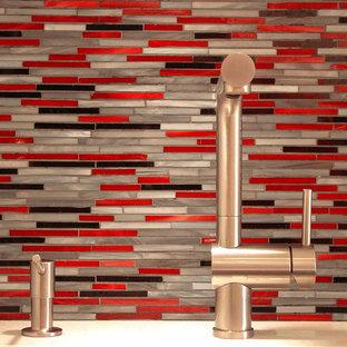 ニューヨークの中サイズのコンテンポラリースタイルのおしゃれなキッチン (アンダーカウンターシンク、フラットパネル扉のキャビネット、白いキャビネット、大理石カウンター、赤いキッチンパネル、ガラスタイルのキッチンパネル、シルバーの調理設備の、セラミックタイルの床、アイランドなし、黒い床) の写真