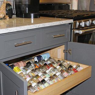 Amerikansk inredning av ett litet kök, med en rustik diskho, bänkskiva i kvartsit, grått stänkskydd, stänkskydd i tunnelbanekakel, rostfria vitvaror, skåp i shakerstil, grå skåp, korkgolv och brunt golv