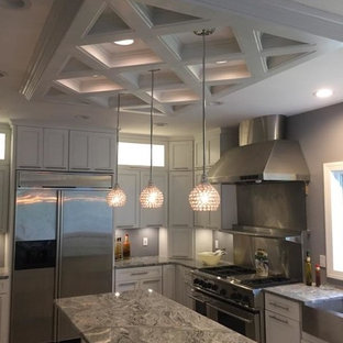 Design ideas for a large shabby-chic style u-shaped eat-in kitchen in Philadelphia with a farmhouse sink, glass-front cabinets, white cabinets, granite benchtops, porcelain splashback, stainless steel appliances, porcelain floors and a peninsula.