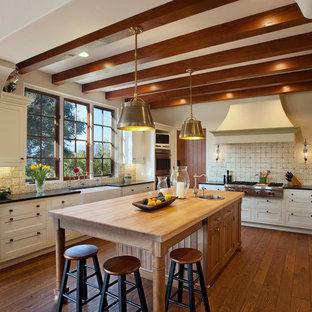 サンタバーバラの中サイズの地中海スタイルのおしゃれなアイランドキッチン (エプロンフロントシンク、白いキャビネット、木材カウンター、パネルと同色の調理設備、無垢フローリング、シェーカースタイル扉のキャビネット、マルチカラーのキッチンパネル、オレンジの床) の写真