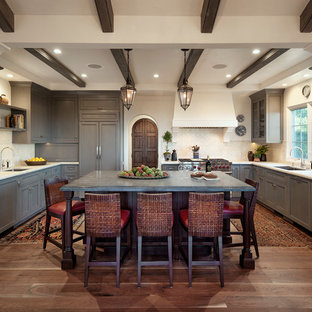 Example of a large tuscan u-shaped medium tone wood floor and brown floor kitchen design in Santa Barbara with gray cabinets, marble countertops, white backsplash, ceramic backsplash, paneled appliances, an island, a double-bowl sink and shaker cabinets