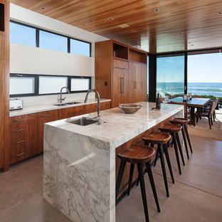 Offene, Mittelgroße Maritime Küche mit Unterbauwaschbecken, flächenbündigen Schrankfronten, hellbraunen Holzschränken, Marmor-Arbeitsplatte, Elektrogeräten mit Frontblende, Betonboden, Kücheninsel und grauem Boden in Los Angeles