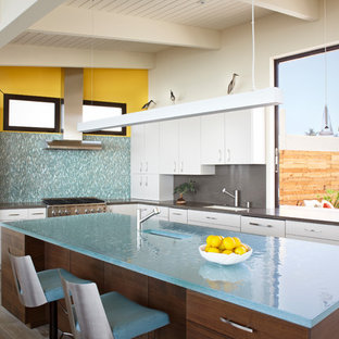 Inspiration for a mid-sized midcentury l-shaped open plan kitchen in Santa Barbara with an undermount sink, flat-panel cabinets, white cabinets, glass benchtops, blue splashback, glass tile splashback, stainless steel appliances, light hardwood floors, with island and grey floor.