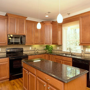 This is an example of a mid-sized traditional u-shaped separate kitchen in Raleigh with a double-bowl sink, recessed-panel cabinets, medium wood cabinets, granite benchtops, black splashback, ceramic splashback, black appliances, light hardwood floors and with island.