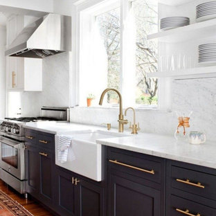 Mid-sized modern single-wall kitchen in Columbus with a farmhouse sink, flat-panel cabinets, black cabinets, quartz benchtops, white splashback, marble splashback, stainless steel appliances, medium hardwood floors, multiple islands, brown floor and white benchtop.