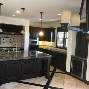 Photo of a mid-sized transitional u-shaped open plan kitchen in Orange County with an undermount sink, recessed-panel cabinets, dark wood cabinets, granite benchtops, beige splashback, stone tile splashback, stainless steel appliances, travertine floors, with island, beige floor and green benchtop.