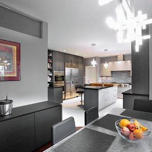 Modelo de cocina comedor en U, moderna, grande, con armarios con paneles lisos, puertas de armario grises, encimera de acrílico, salpicadero metalizado, salpicadero de metal, electrodomésticos de acero inoxidable, suelo laminado y una isla