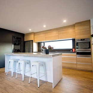 Inspiration for a mid-sized contemporary galley kitchen pantry in Hobart with a drop-in sink, louvered cabinets, light wood cabinets, concrete benchtops, black splashback, ceramic splashback, stainless steel appliances, light hardwood floors and with island.