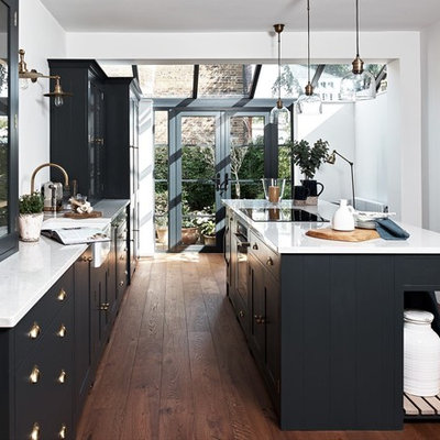 Example of a mid-sized transitional galley dark wood floor and brown floor enclosed kitchen design in Kent with a farmhouse sink, granite countertops, white backsplash, paneled appliances, an island, shaker cabinets and gray cabinets