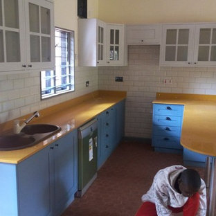 Inspiration for a mid-sized midcentury u-shaped eat-in kitchen in Other with an undermount sink, recessed-panel cabinets, turquoise cabinets, marble benchtops, yellow splashback, marble splashback, black appliances, terra-cotta floors, no island, brown floor and yellow benchtop.