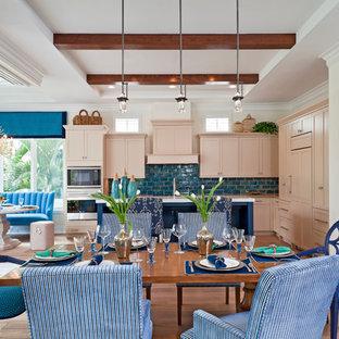 Foto de cocina comedor en L, tropical, con armarios con paneles empotrados, puertas de armario beige, salpicadero azul, electrodomésticos de acero inoxidable, fregadero bajoencimera, encimera de cuarcita, salpicadero de azulejos tipo metro, suelo de madera clara y una isla