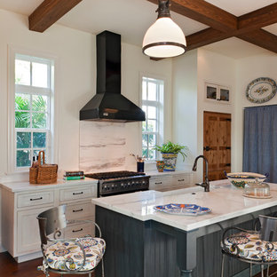 Inspiration for a cottage galley dark wood floor eat-in kitchen remodel in Miami with a farmhouse sink, recessed-panel cabinets, white cabinets, white backsplash, stainless steel appliances, quartzite countertops, stone slab backsplash and an island