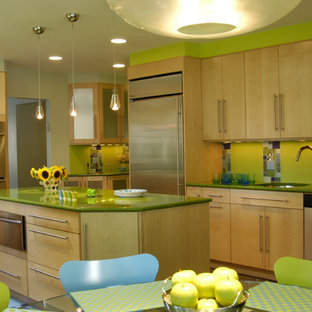 This is an example of a mid-sized eclectic l-shaped eat-in kitchen in New York with glass tile splashback, stainless steel appliances, green splashback, flat-panel cabinets, light wood cabinets, an undermount sink, quartz benchtops, ceramic floors, with island and green benchtop.