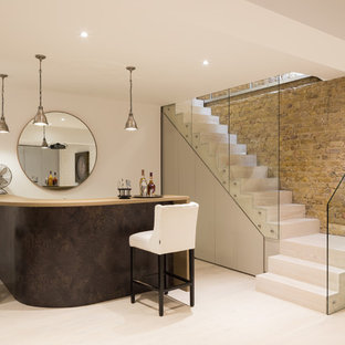 This is an example of a medium sized contemporary kitchen in London with light hardwood flooring.