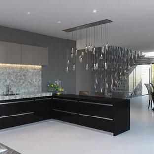 ブリスベンの広いコンテンポラリースタイルのおしゃれなキッチン (フラットパネル扉のキャビネット、黒いキャビネット、コンクリートの床、ドロップインシンク、オニキスカウンター、グレーのキッチンパネル、大理石のキッチンパネル、シルバーの調理設備、白い床、黒いキッチンカウンター) の写真