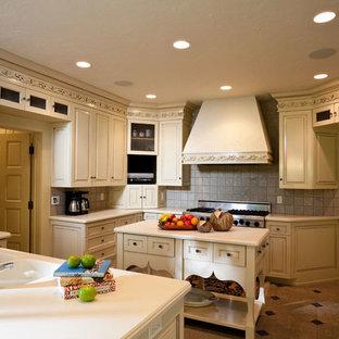 他の地域の大きいヴィクトリアン調のおしゃれなキッチン (ドロップインシンク、インセット扉のキャビネット、ベージュのキャビネット、グレーのキッチンパネル、シルバーの調理設備の) の写真