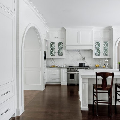 Example of a classic kitchen design in Detroit with glass-front cabinets, white cabinets, white backsplash, stainless steel appliances and marble backsplash