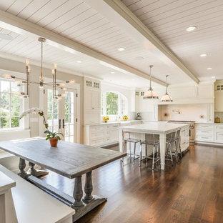 Foto di una cucina chic con ante con riquadro incassato, ante bianche, paraspruzzi bianco, elettrodomestici in acciaio inossidabile, parquet scuro e isola