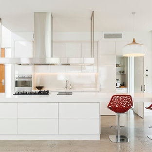 Photo of a contemporary galley kitchen in Adelaide with a double-bowl sink, flat-panel cabinets, white cabinets, white splashback, stainless steel appliances, concrete floors and an island.