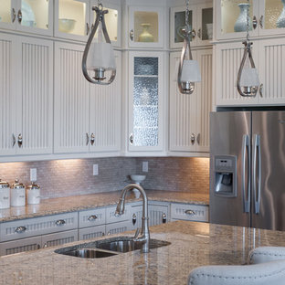Photo of a mid-sized country single-wall eat-in kitchen in Jacksonville with a double-bowl sink, louvered cabinets, white cabinets, marble benchtops, beige splashback, stone tile splashback, stainless steel appliances, vinyl floors and with island.