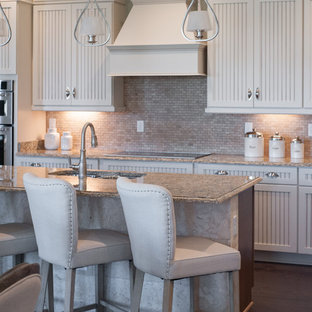 Mid-sized country single-wall eat-in kitchen in Jacksonville with a double-bowl sink, louvered cabinets, white cabinets, marble benchtops, beige splashback, stone tile splashback, stainless steel appliances, vinyl floors and with island.