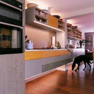Inspiration for a mid-sized contemporary galley open plan kitchen in London with an integrated sink, flat-panel cabinets, yellow cabinets, laminate benchtops, metallic splashback, stainless steel appliances, medium hardwood floors, with island, brown floor and white benchtop.