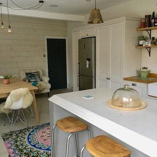 他の地域の中くらいのエクレクティックスタイルのおしゃれなキッチン (エプロンフロントシンク、シェーカースタイル扉のキャビネット、グレーのキャビネット、大理石カウンター、ピンクのキッチンパネル、セメントタイルのキッチンパネル、シルバーの調理設備、セラミックタイルの床、ベージュの床) の写真