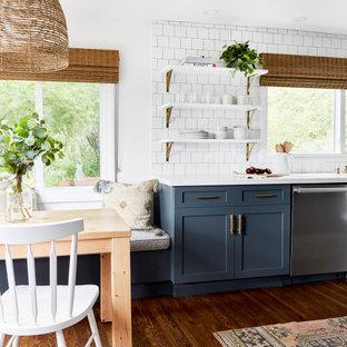 Mittelgroße Maritime Wohnküche mit Schrankfronten im Shaker-Stil, blauen Schränken, Quarzwerkstein-Arbeitsplatte, Küchenrückwand in Weiß, Rückwand aus Metrofliesen, Küchengeräten aus Edelstahl, weißer Arbeitsplatte und braunem Holzboden in Los Angeles