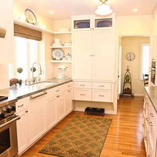 Inspiration for a mid-sized shabby-chic style galley separate kitchen in San Diego with an undermount sink, shaker cabinets, white cabinets, quartz benchtops, white splashback, subway tile splashback, panelled appliances, medium hardwood floors, no island and brown floor.