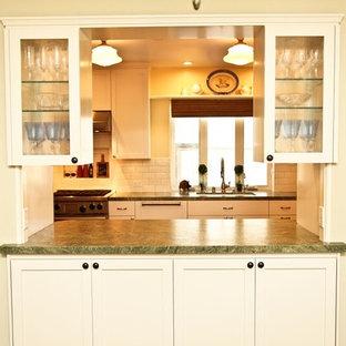 サンディエゴの中サイズのシャビーシック調のおしゃれなキッチン (アンダーカウンターシンク、シェーカースタイル扉のキャビネット、白いキャビネット、クオーツストーンカウンター、白いキッチンパネル、サブウェイタイルのキッチンパネル、パネルと同色の調理設備、無垢フローリング、アイランドなし、茶色い床) の写真