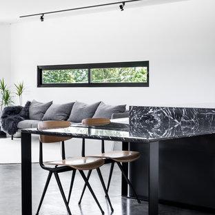 Immagine di una piccola cucina moderna con lavello a vasca singola, ante a persiana, ante nere, top in marmo, paraspruzzi bianco, paraspruzzi con piastrelle in ceramica, elettrodomestici in acciaio inossidabile, pavimento in cemento e 2 o più isole