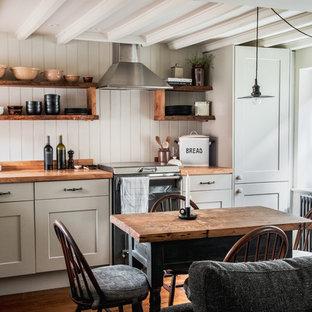 Diseño de cocina comedor en L, campestre, pequeña, con fregadero sobremueble, encimera de madera, suelo de madera en tonos medios, armarios estilo shaker, suelo marrón y encimeras marrones