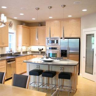 Cette image montre une grande cuisine américaine design en L avec un placard à porte shaker, des portes de placard en bois clair, une crédence grise, un électroménager en acier inoxydable, un évier encastré, un plan de travail en quartz modifié, un sol en bambou et un îlot central.