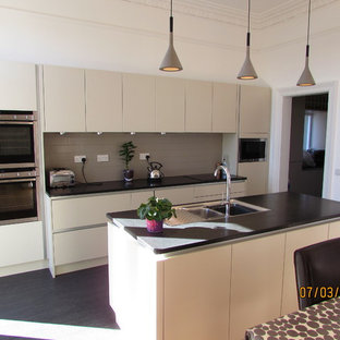 Design ideas for a mid-sized modern single-wall eat-in kitchen in Edinburgh with an undermount sink, flat-panel cabinets, beige cabinets, solid surface benchtops, grey splashback, porcelain splashback, stainless steel appliances, vinyl floors and with island.