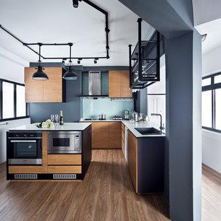 Industrial Küche in L-Form mit flächenbündigen Schrankfronten, hellen Holzschränken, Glasrückwand, Küchengeräten aus Edelstahl, hellem Holzboden und Kücheninsel in Singapur