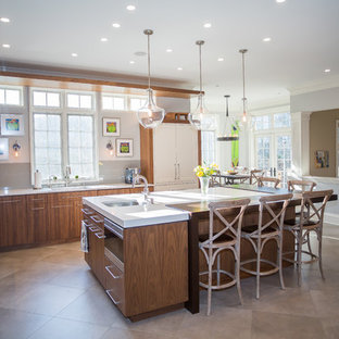 Photo of a large transitional l-shaped open plan kitchen in DC Metro with an undermount sink, flat-panel cabinets, medium wood cabinets, beige splashback, stainless steel appliances, with island, beige floor, solid surface benchtops, glass tile splashback, cement tiles and white benchtop.